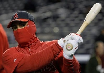 Kendry Morales takes batting practice with face covered in the cold.JPG
