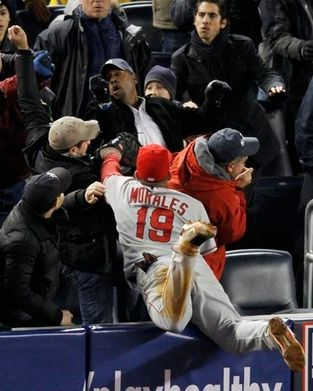 Kendry Morales dives into the stands to try and catch a foul ball.JPG