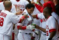maicer izturis congratulated in dugout.jpg